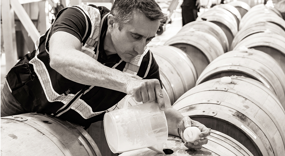 Winemakers topping off barrel